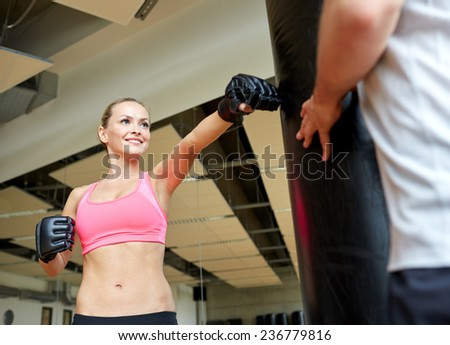 sport, fitness, lifestyle and people concept - smiling woman with personal trainer boxing punching bag in gym - stock photo