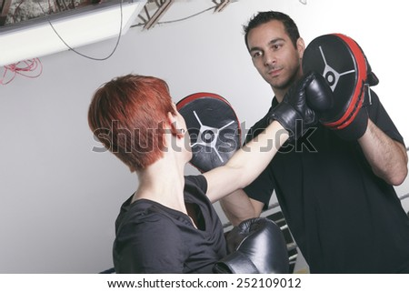 sport, fitness, lifestyle and people concept - woman with personal trainer boxing punching bag in gym - stock photo