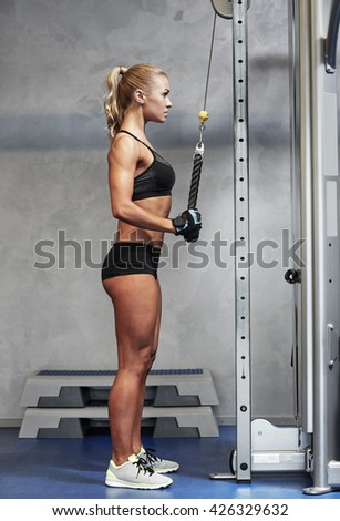 sport, fitness, lifestyle and people concept - young woman flexing muscles on cable gym machine - stock photo