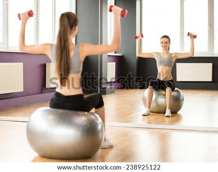 Sport, fitness, lifestyle concept. Smiling woman with exercise ball and dumbbells in gym. Back view. - stock photo