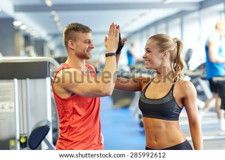 sport, fitness, lifestyle, gesture and people concept - smiling man and woman doing high five in gym - stock photo