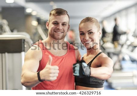 sport, fitness, lifestyle, gesture and people concept - smiling man and woman showing thumbs up in gym - stock photo