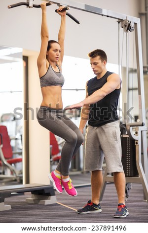 sport, fitness, lifestyle, teamwork and people concept - young woman with trainer hanging on bar and doing leg raises in gym - stock photo