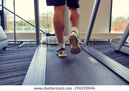 sport, fitness, lifestyle, technology and people concept - close up of man legs walking on treadmill in gym from back - stock photo