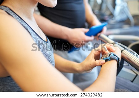 sport, fitness, lifestyle, technology and people concept - close up of woman setting heart-rate watch at gym with trainer - stock photo