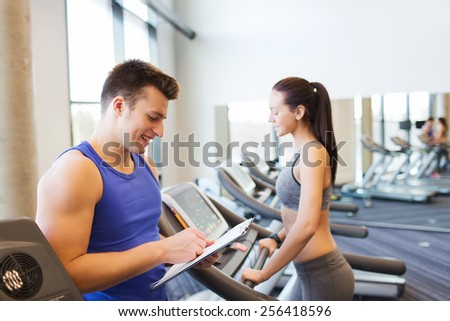 sport, fitness, lifestyle, technology and people concept - happy woman and trainer with clipboard working out on treadmill in gym - stock photo