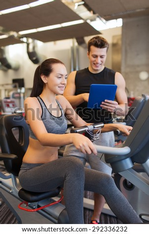 sport, fitness, lifestyle, technology and people concept - happy woman and trainer with tablet pc computer working out on exercise bike in gym - stock photo
