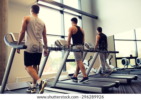 sport, fitness, lifestyle, technology and people concept - men exercising on treadmill in gym