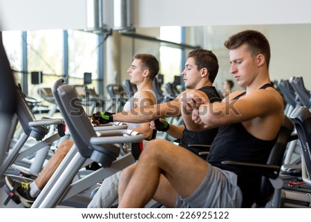 sport, fitness, lifestyle, technology and people concept - men working out on exercise bike in gym