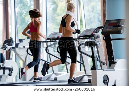sport, fitness, lifestyle, technology and people concept - smiling woman exercising on treadmill in gym - stock photo