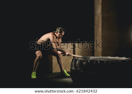 Sport Fitness Man Hitting Wheel Tire With Hammer Sledge Cross fit Training, Young Healthy Guy Gym Interior