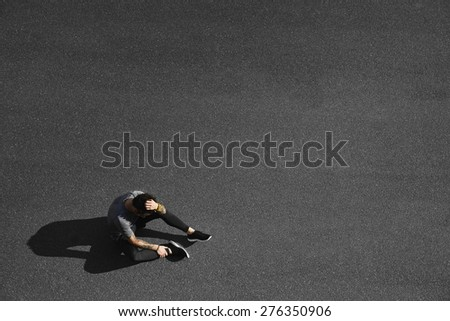 Sport fitness man relaxing after training. Young male athlete resting sitting in asphalt after running and training exercise outside in summer. Caucasian man sports model. - stock photo