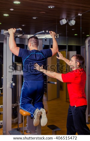 sport, fitness, teamwork, bodybuilding people concept - man and personal trainer with barbell weight lifting group weightlifting workout exercise gym. - stock photo