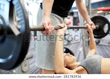 sport, fitness, teamwork, weightlifting and people concept - close up of young woman and personal trainer with barbell flexing muscles in gym - stock photo