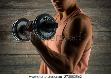 sport, fitness, weightlifting, bodybuilding and people concept - close up of young man with dumbbell flexing biceps over wooden wall background - stock photo
