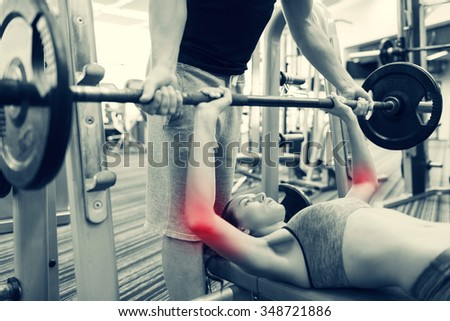 sport, fitness, weightlifting, sports injury and people concept - young woman and personal trainer with barbell flexing muscles in gym - stock photo