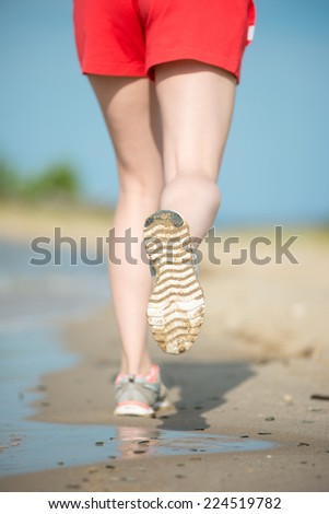 Sport footwear, sand footprints and legs close up. Runner feet detail. Workout near ocean sea coast. Beautiful fit girl. Fitness model caucasian ethnicity outdoors. Weight loss exercise. Jogging. - stock photo
