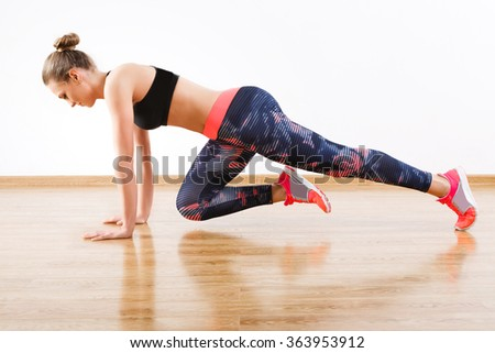 Sport girl with dark hair wearing pink snickers, dark leggings and black short top doing full plank with bent leg at gym, fitness, white wall and wooden floor. - stock photo