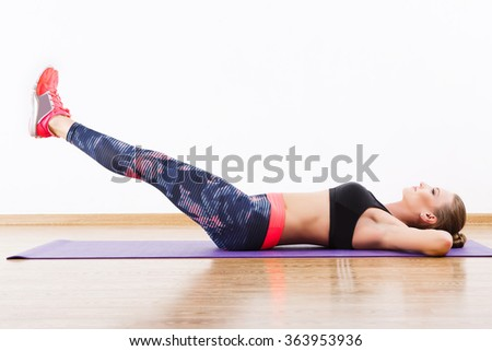 Sport girl with dark hair wearing pink snickers, dark leggings and black short top doing leg raise at gym, fitness, white wall and wooden floor. - stock photo