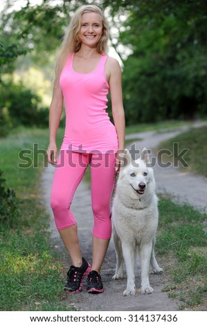 Sport girl with Huskies in a park - stock photo