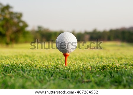 Sport, Golf concept - Golf ball on a tee against the golf course. Close up at golf ball and tee  - stock photo
