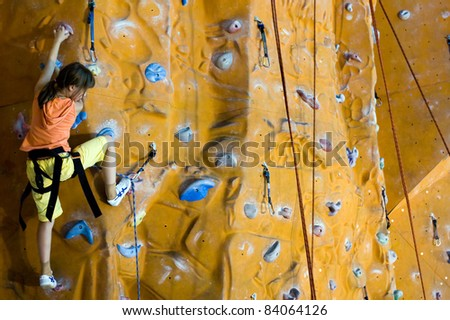 Sport image of climbing teenager (little girls) to the top of wall - stock photo