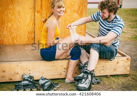 Sport injury. Couple of skaters outdoor. Young woman suffering from leg pain after taking a fall on the asphalt, man is helping bandaging her injured knee - stock photo