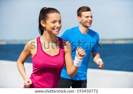 Sport is our life.  Cheerful young woman and man in sports clothing running along the riverbank  and smiling - stock photo