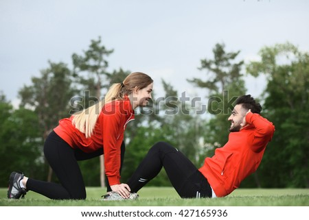 Sport lady holding man's legs who is doing abdominal crunches on fresh air in green park or forest. Fitness man preparing for competitions. - stock photo