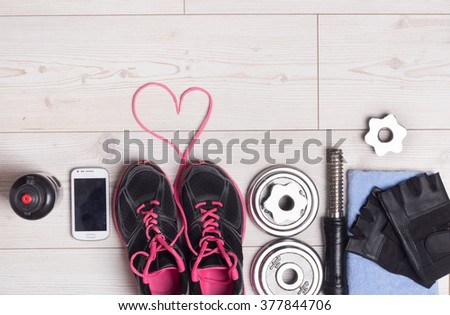 Sport lifestyle concept. Top view of dumbbells, sneakers and sport accessories on the bright wooden floor. Heart shape with shoe laces - stock photo
