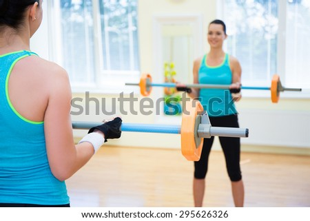 sport lifting concept - young woman exercising with barbell in gym - stock photo
