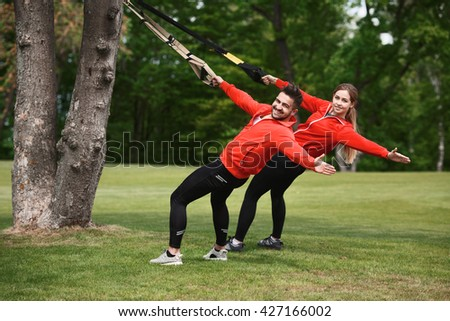Sport man and woman training with help of suspension trainer sling near green tree. Happy couple doing sports exercises in green park.