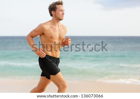 Sport man running. Male athlete runner jogging shirtless training on beautiful beach. Fit handsome male fitness model jogging alone training for marathon run. Caucasian man in his twenties. - stock photo