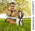 sport man stretching at the park - fitness concepts / Young man sports exercises. - stock photo