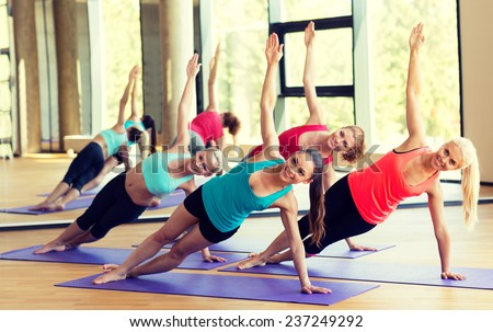 sport, meditation and lifestyle concept - smiling women meditating on mat in gym - stock photo