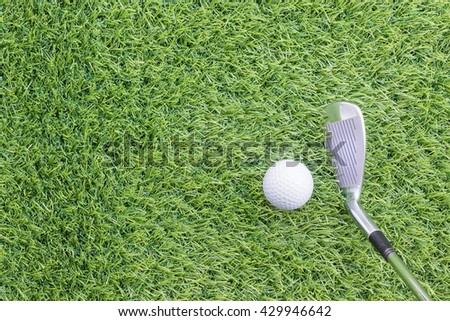 Sport objects related to golf equipment ,Golf club and ball on green grass - stock photo