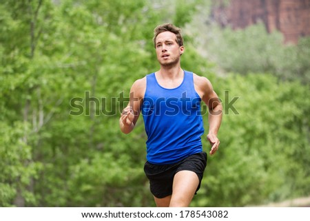 Sport running fitness man training towards goals. Fit male runner sprinting and jogging training outside in forest for marathon run. Muscular handsome Caucasian model in his 20s. - stock photo
