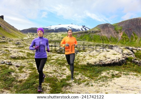 Sport running. Runners on cross country trail outdoors working out for marathon. Fit young fitness model man and asian woman training together outside in mountain nature on Snaefellsnes, Iceland. - stock photo