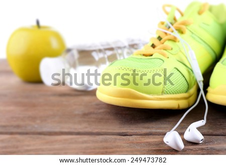Sport shoes and bottle of water on light background - stock photo