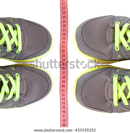 Sport shoes and centimeter as a fitness running. Sport shoes and pink measure tape isolated on white background. - stock photo