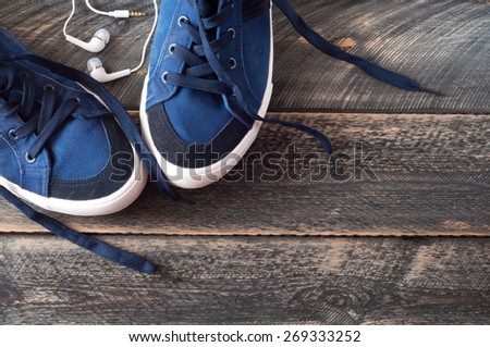 Sport shoes and earphones on old wooden background . Top view. Selective focus - stock photo