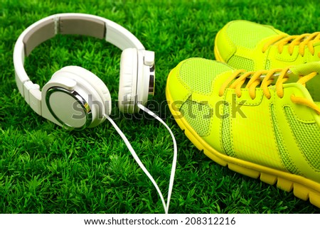 Sport shoes and headphones on green grass background - stock photo