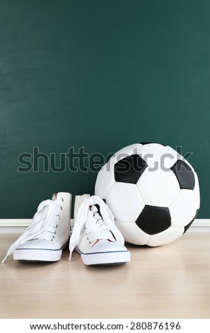 Sport shoes and soccer ball on blackboard background - stock photo