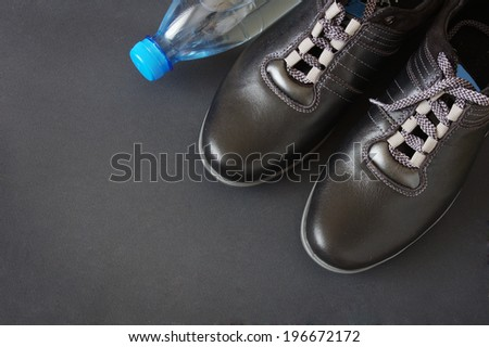 Sport shoes and water on black background - stock photo