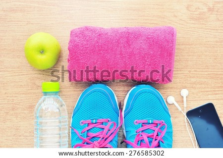 Sport shoes and water with set for sports activities on tiled floor. - stock photo