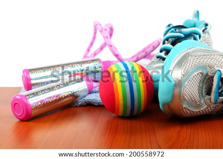 Sport shoes, ball and jump rope on a wooden background. - stock photo