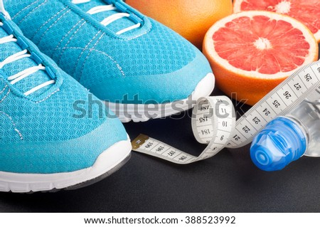 Sport shoes, grapefruit, bottle of water and measuring tape on dark background. Sport sportswear. Concept healthy lifestyle, sport and diet. Selective focus - stock photo