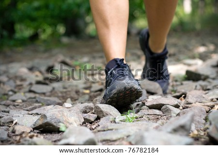 Sport shoes on trail walking running in mountains. Jogging or training outside in summer nature, motivational health and fitness concept. - stock photo