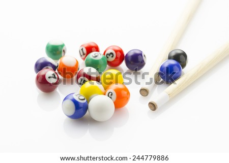 sport snooker balls with cues laying on white reflective background