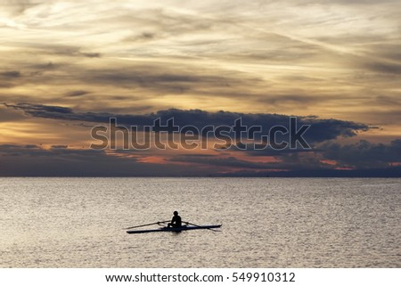 Sport. Solitary rower during his training session in the sunset light.